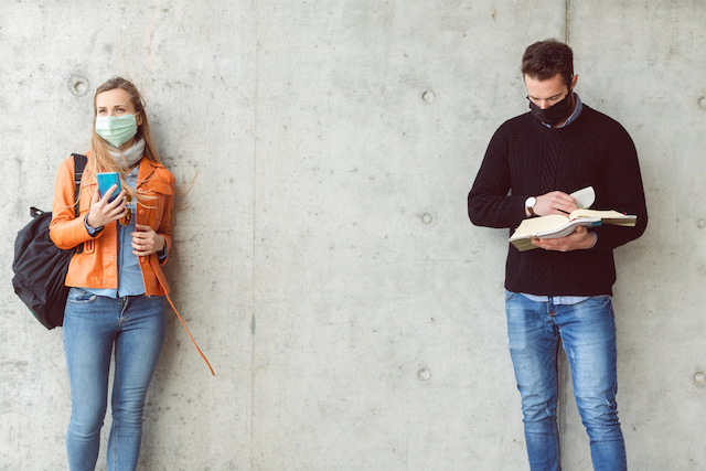 A woman student wearing a face mask looks at her phone while a few feet away a male student wearing a face mask looks at a book.