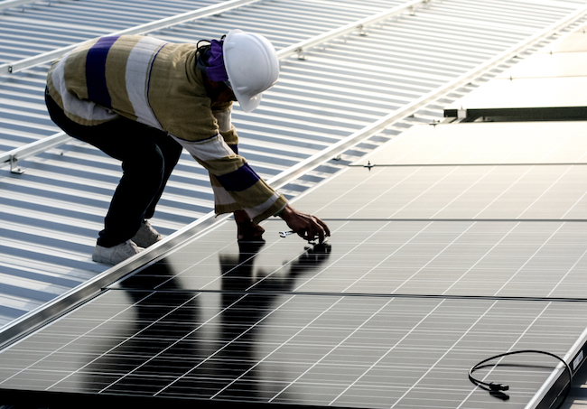 Worker on roof adjusting solar panels.