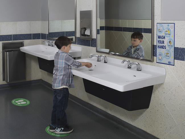 Student washing hands with touchless faucet.