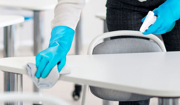 Someone with blue rubber gloves wiping down a desk.